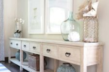 03 a long whitewashed console with sea-inspired artworks, large bottles and lanterns and shells
