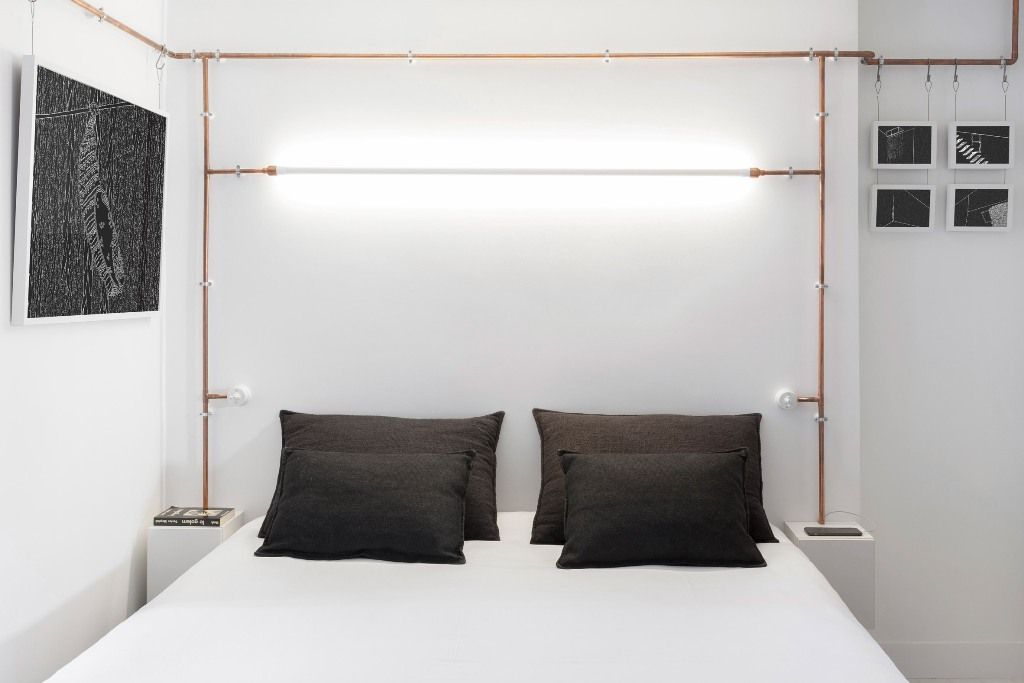 In the sleeping zone copper pipes hold bulbs and lamps and monochrome artworks hanging around