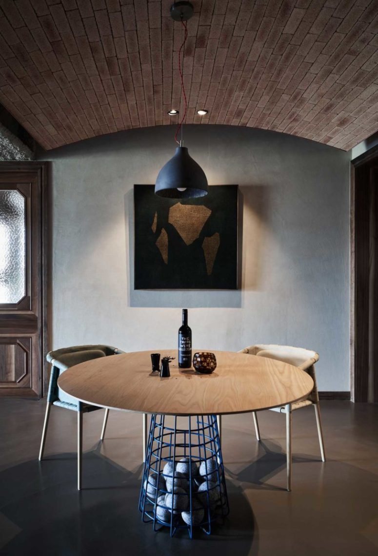 The dining space features artworks and a creative table with rocks inside the ethereal base