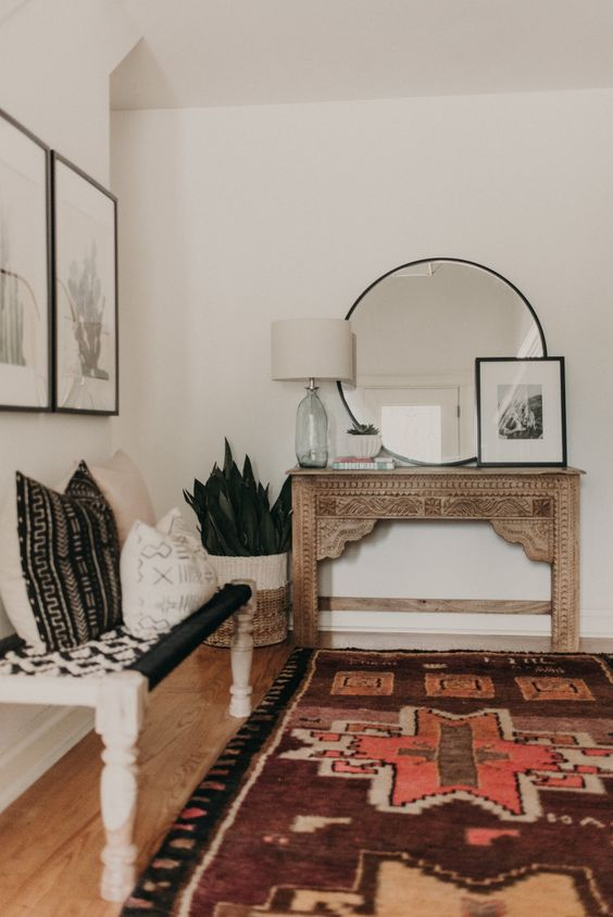 a boho entryway with a vintage encrusted console, a woven bench, pillows, artworks and succulents