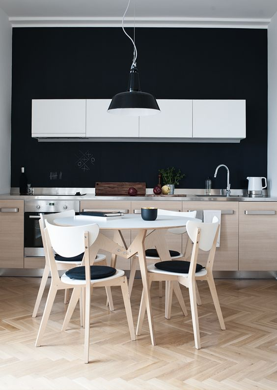 a contemporary kitchen with pale wood and white furniture and a chalkboard backsplash and blakc touches for a stylish look