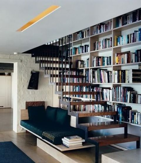 a cozy reading nook with built-in shelves into the wall and an upholstered beach for reading