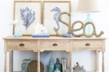 04 a light-colored wooden console, a rope artwork, painted bottles and a duo of sea creature artworks