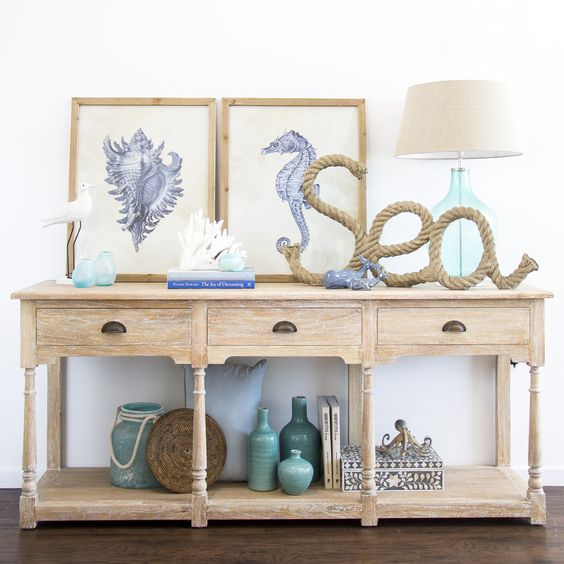 a light colored wooden console, a rope artwork, painted bottles and a duo of sea creature artworks