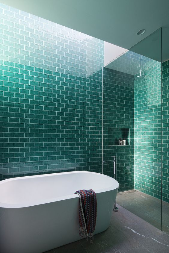 a modern bathroom with turquoise tiles and white grout for a bold space with a splash of color