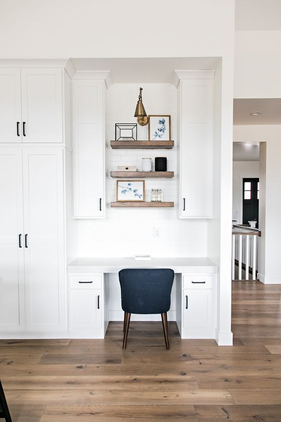 a modern farmhouse space with a seamless home office nook with cabinets, built-in shelves and a black chair