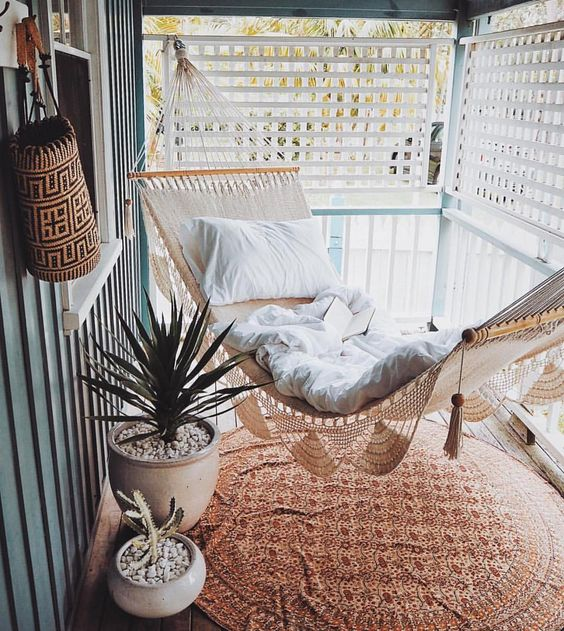 a small screened porch with a woven hammock, potted succulents and a boho printed rug