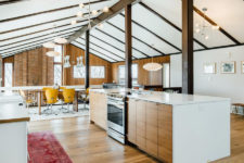 05 The upper part contains ad kitchen with white and light-colored wood furniture and a dining zone with a wooden table and yellow chairs