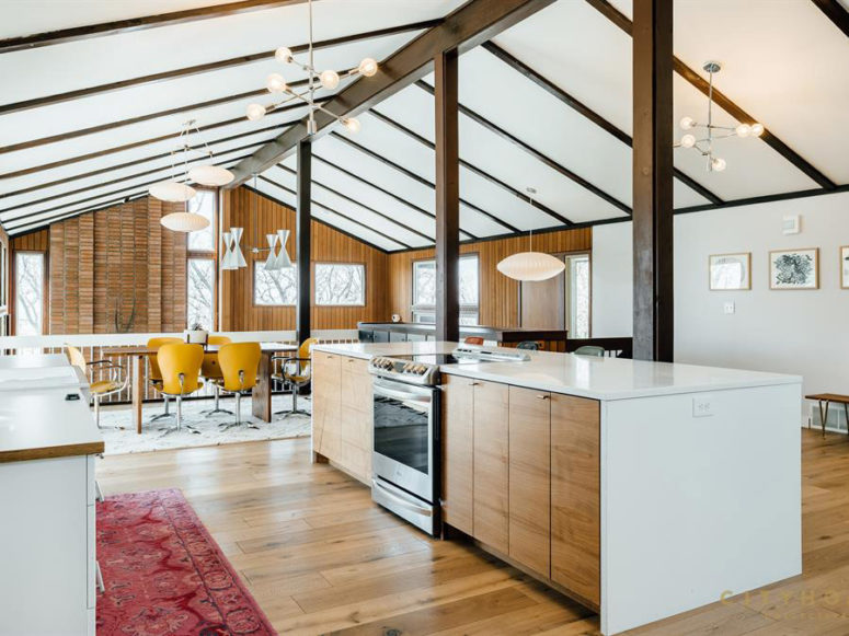 The upper part contains ad kitchen with white and light-colored wood furniture and a dining zone with a wooden table and yellow chairs