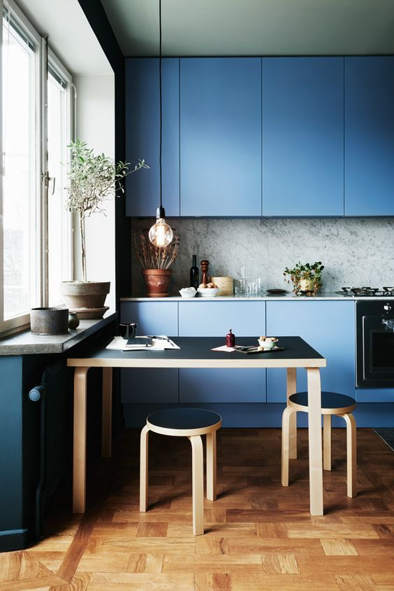 a blue minimalist kitchen with a grey marble backsplash and a black dining set for a gorgeous look