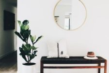 05 a boho rug, a woven leather bench, a faux fur pillow, a round mirror, a potted plant are an ideal combo