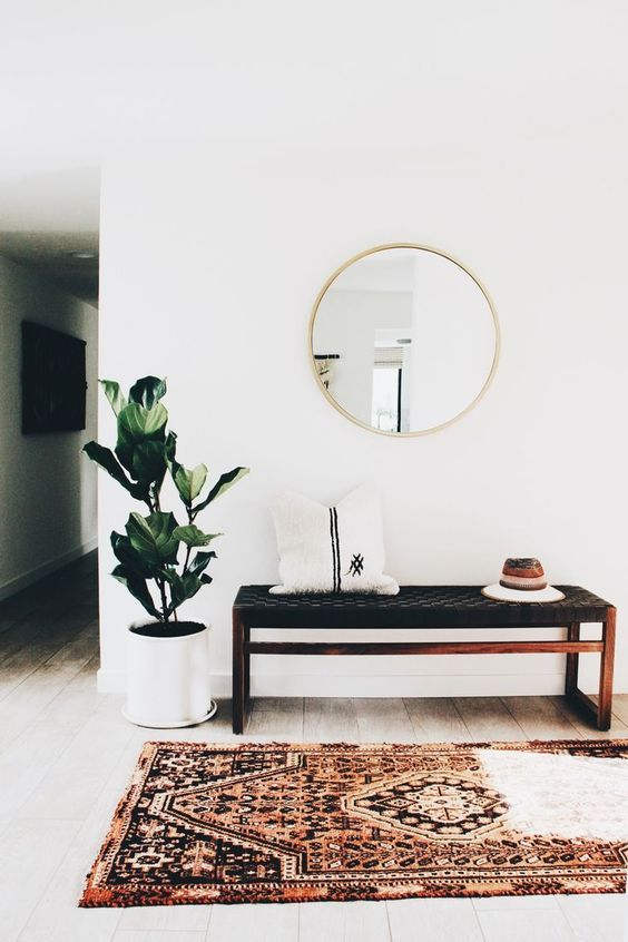 a boho rug, a woven leather bench, a faux fur pillow, a round mirror, a potted plant are an ideal combo
