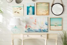 05 a coastal entryway with a gallery wall of artworks, a white vintage console, a mirror and some screws