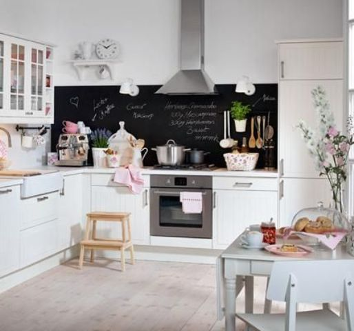 a cute white kitchen with a chalkboard backsplash and a mint dining set for a chic look