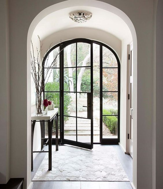 a fully glazed arched door with black metal framing is a chic and refined idea for any home