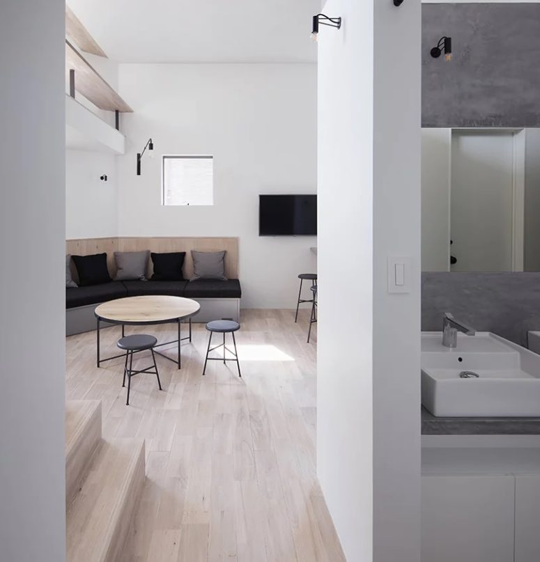 The bathroom is clad with concrete and whites, it's also ultra-minimalist