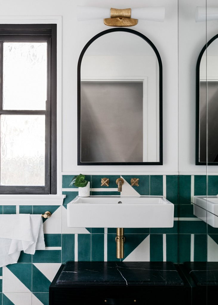 The bathroom is done with amazing green geometric tiles, black marble touches and brass fixtures