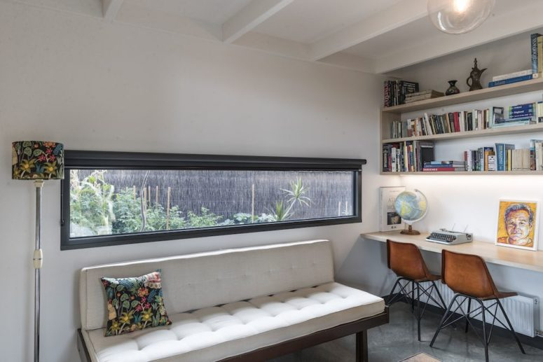 The home office is done with a long narrow window, a shared office space and an upholstered bench