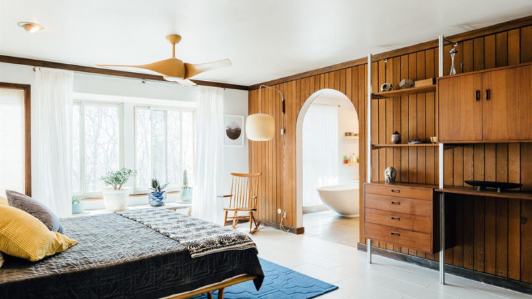 The master bedroom is done with mid-century modern furniture, a wood clad wall with an arched walkway to the bathroom