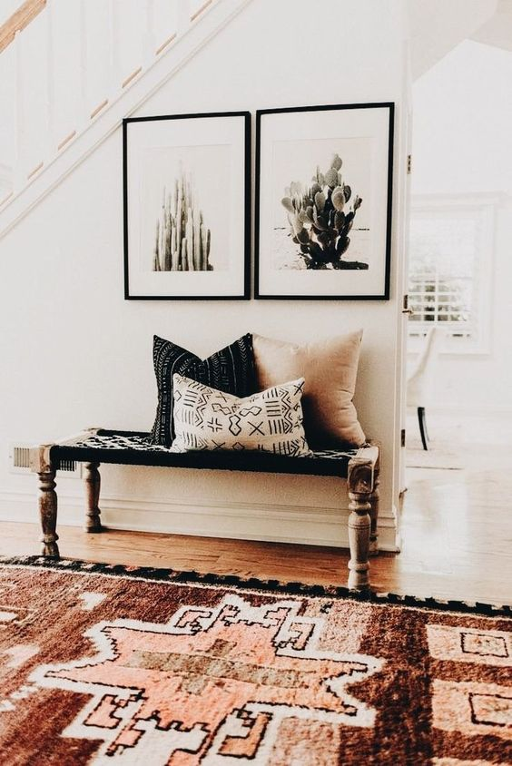 a boho rug, a woven bench and cacti artworks for a desert boho feel