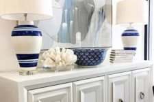 06 a chic white console, a large watercolor ocean-inspired artwork, striped lamps and a coral for a beach entryway