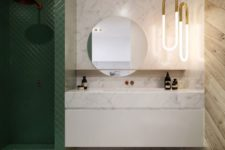 06 a luxurious look is achieved with the use of marble, wood and green tiles that clad the shower space