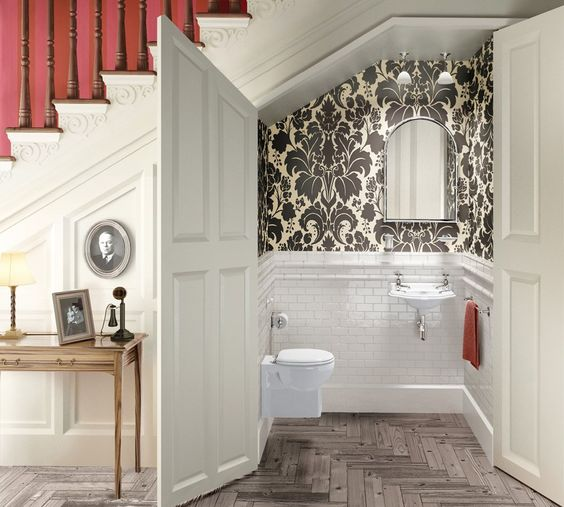 a powder room styled with white tiles and vintage printed wallpaper for a vintage feel