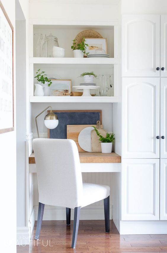 build in a small office nook in your kitchen with shelves and a desk covered with a wooden countertop and a comfy chair
