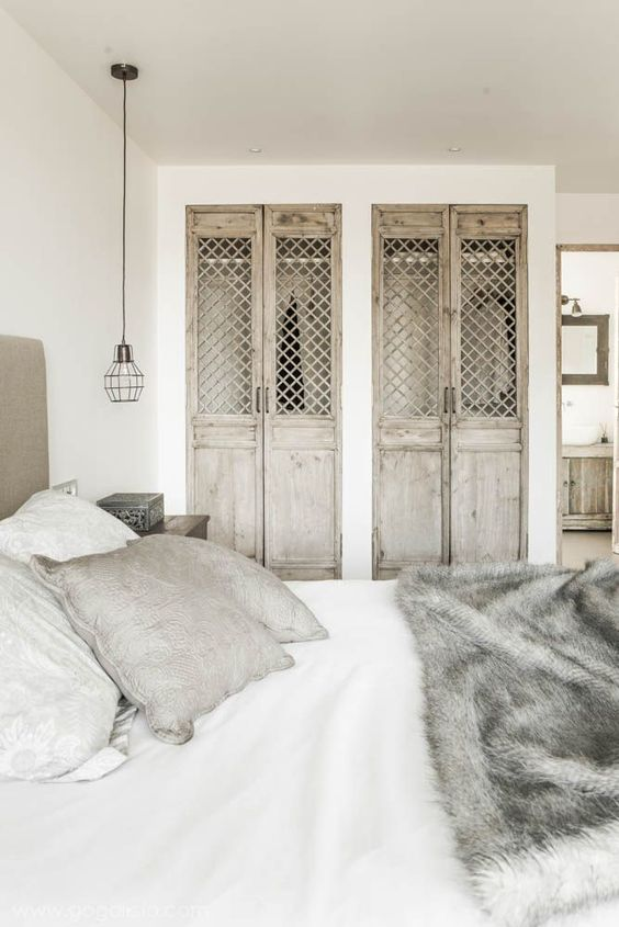 shabby chic wooden doors with wood lettice add interest to this industrial space and spearate the closet