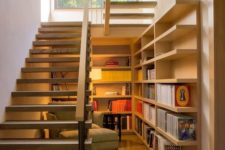 06 under the stairs reading nook with shelves and a comfy lounge chair and enough light