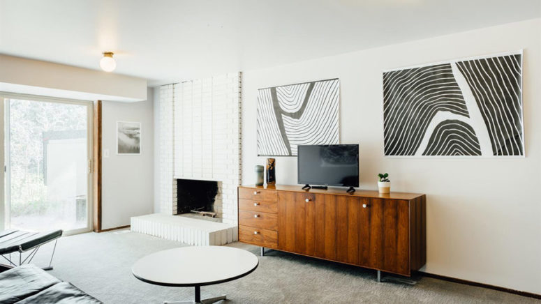 Here's another sitting zone with a brick clad fireplace, monochrome artworks and cool furniture