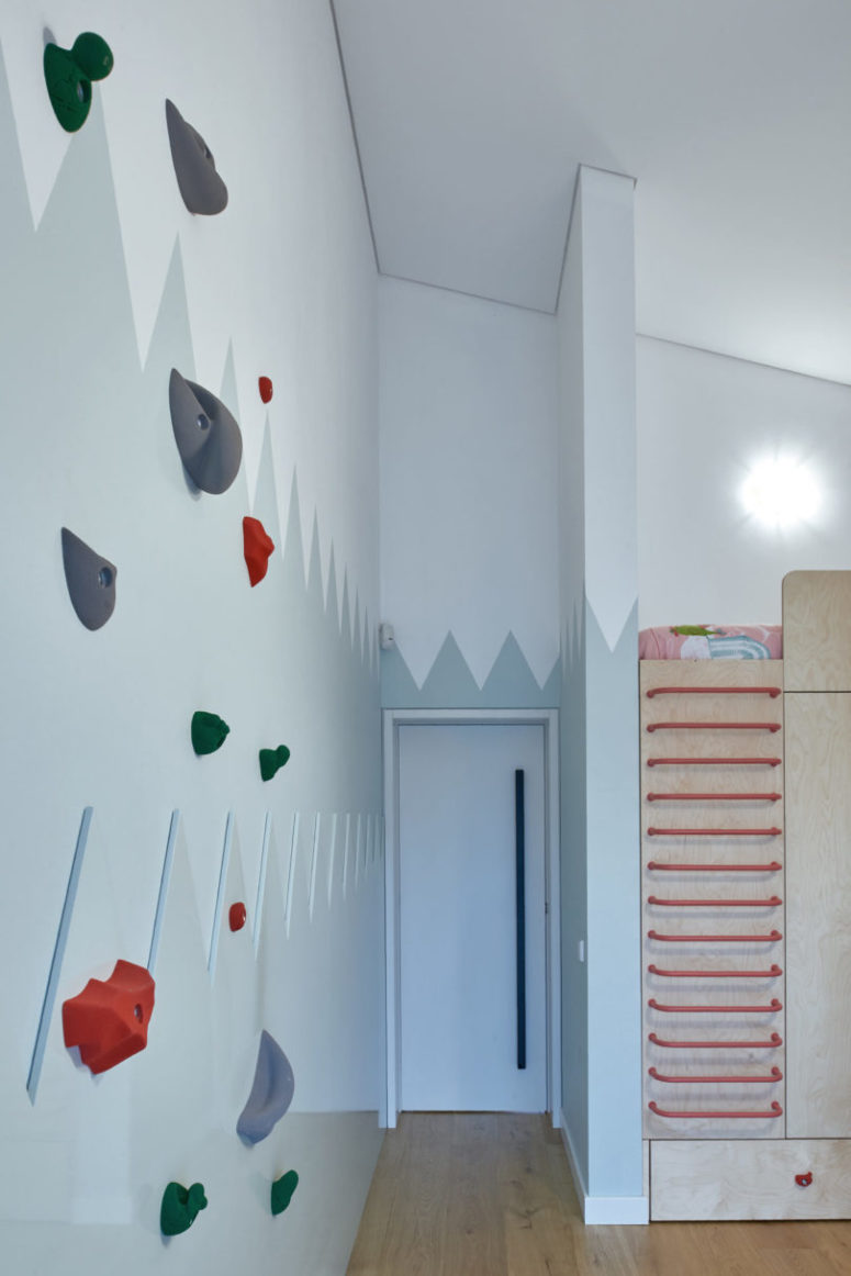 The kid's room is done with a large piece, which includes storage and a bed on top, there's a real climbing wall