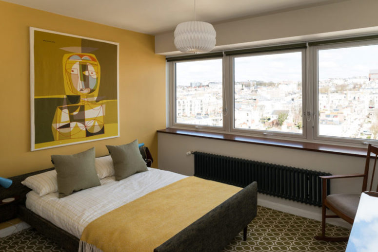 The master bedroom is done in mustard shades, with a large window and a cool artwork