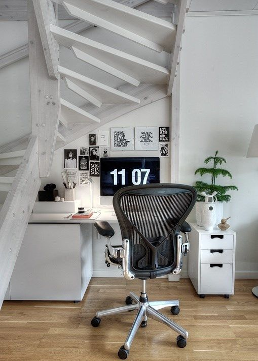 a Scandinavian home office nook under a staircase with no risers, with a comfy desk with much storage and a gorgeous chair