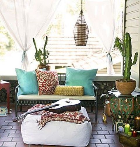 a boho porch with printed and colorful textiles, cacti and candle lanterns