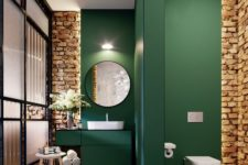 a contemporary bathroom with emerald walls and a space divider and exposed brick for a texture