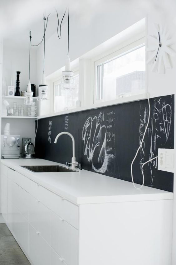 a minimalist white kitchen with a chalkboard backsplash that helps it stand out and look more interesting
