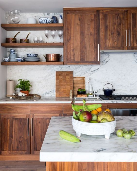 a rich-colored wooden kitchen contrasts the white marble backsplash and countertops and together they create a wow effect