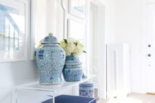 07 an acrylic console and stool with upholstery, artworks and a mirror and painted blue vases