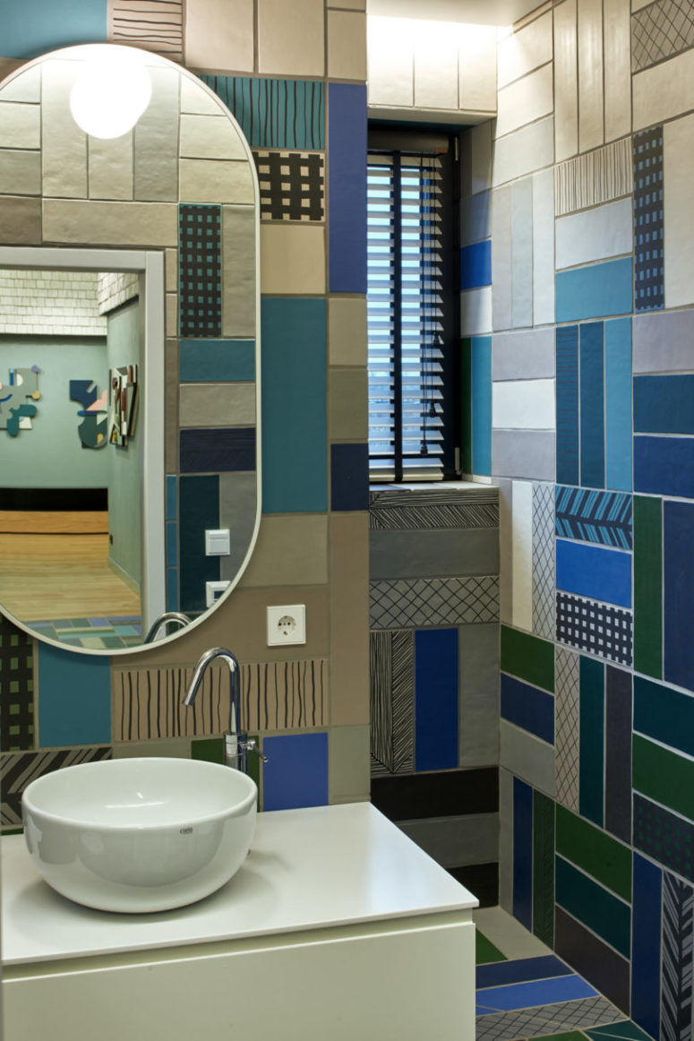 The bathroom is clad with colorful mosaic tiles that remind of the repeated patterns throught the house