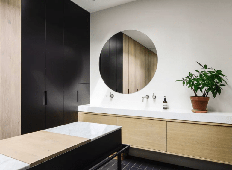 The bathroom is done in black and white with light-colored wood and marble for a chic look