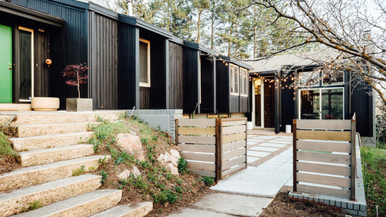 The exterior of the house is clad with black painted wood