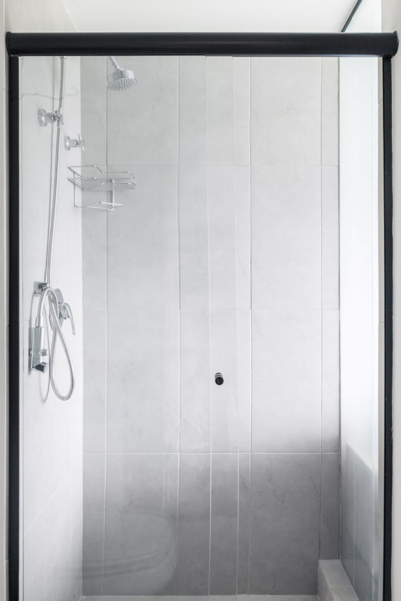 The small bathroom features a comfy shower clad with marble tiles