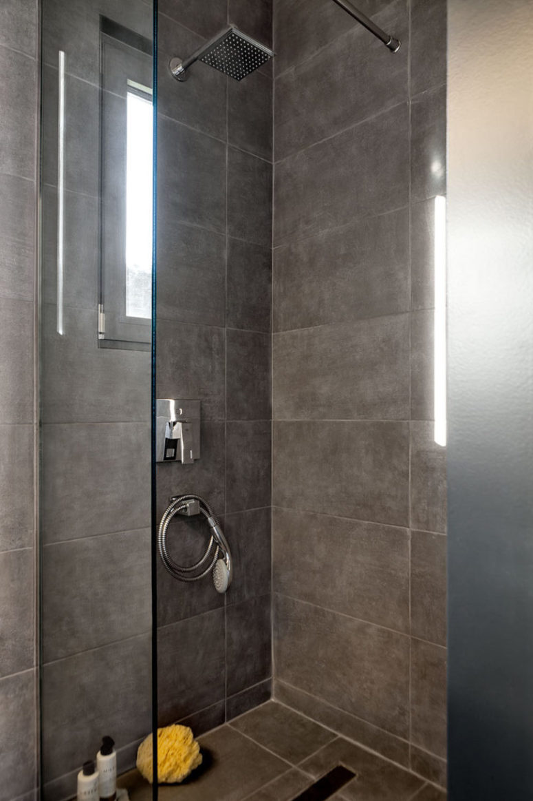 The small bathroom features a concrete clad shower