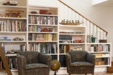 08 a built-in bookcase in the stairs and a couple of upholstered chairs for reading