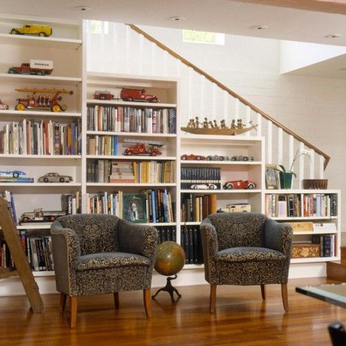 a built-in bookcase in the stairs and a couple of upholstered chairs for reading