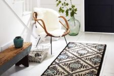 08 a rug, a wood and metal bench, a rattan chair with faux fur, a metal basket