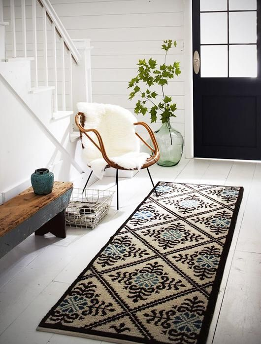 a rug, a wood and metal bench, a rattan chair with faux fur, a metal basket
