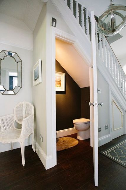 a small powder room with black and white decor, an artwork and a jute rug for a cozy feel