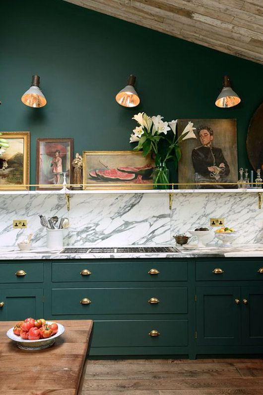 a super elegant vintage kitchen with forest green cabinets and a grey marble backsplash creates a wow effect